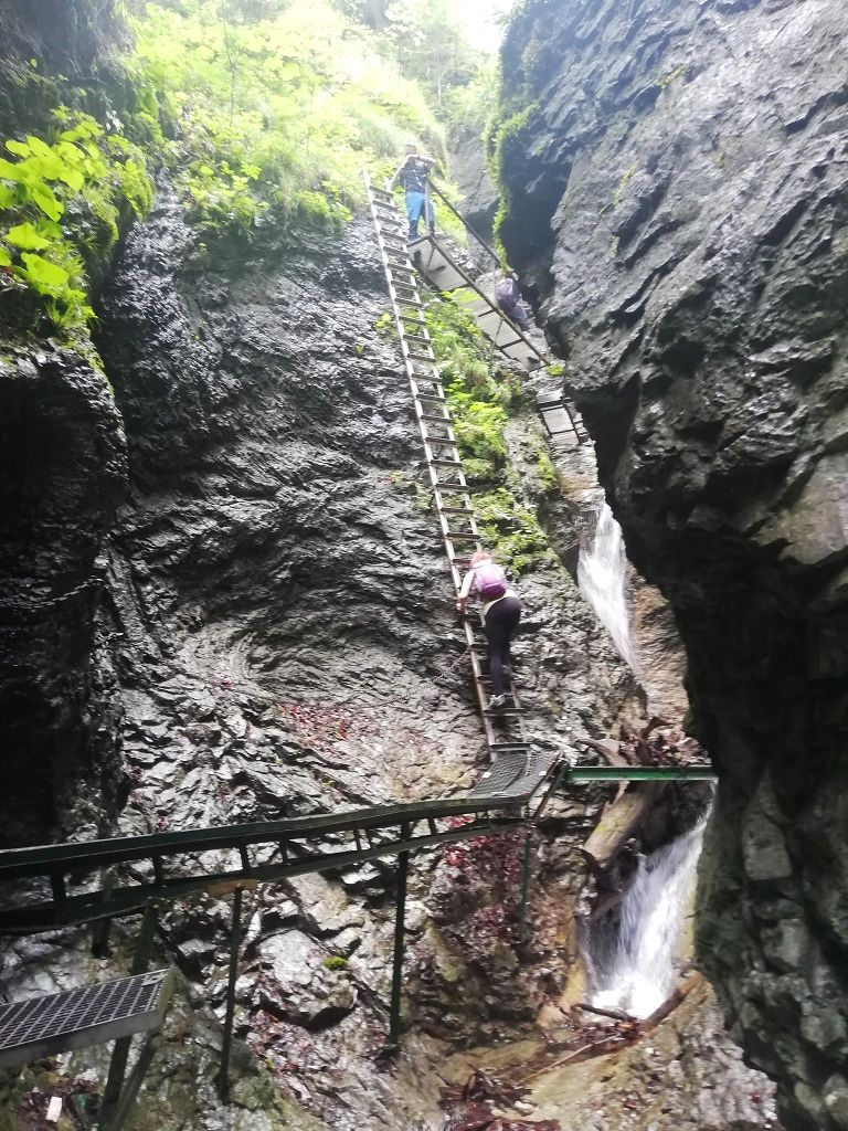 Metal ladders and supports to climb up a cascade (these are random hikers on the picture)